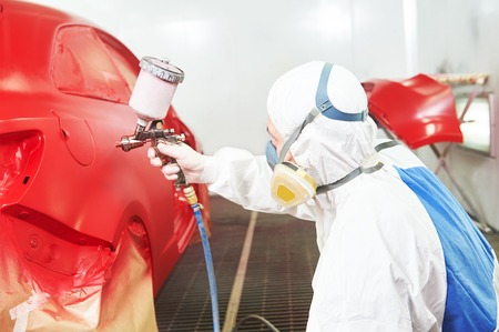 sprays: auto painting worker. red car in a paint chamber during repair work Stock Photo