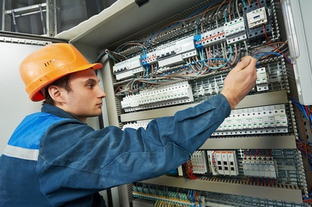 electrician with screwdriver tighten up switching electric actuator equipment in fuse box Archivio Fotografico