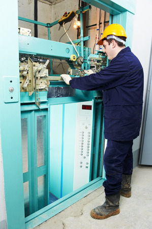 machinist: male technician machinist worker adjusting elevator mechanism of lift with spanner