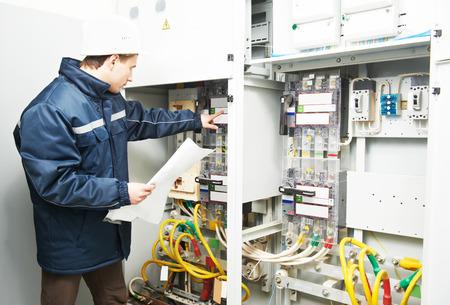 Electricista constructor inspector ingeniero de verificación de los datos de los equipos en la caja de fusibles Foto de archivo - 41782126