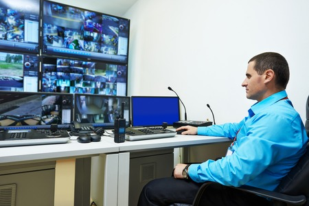 monitoring system: security guard watching video monitoring surveillance security system Stock Photo