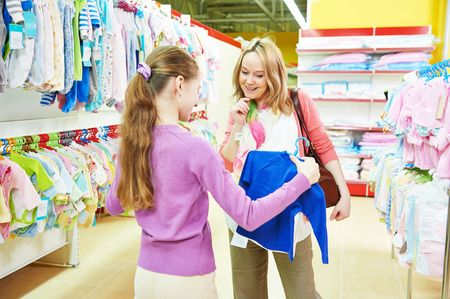 pregnant woman and little girl choosing baby clothes during shopping at garments supermarket