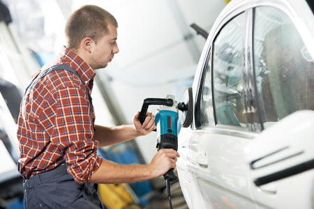 car clean: auto mechanic worker polishing car body at automobile repair and renew service station shop by power buffer machine Stock Photo