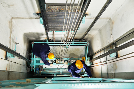 two male technician machinist worker at work adjusting elevator mechanism of lift with spanner Archivio Fotografico