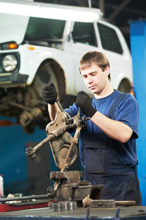lever: automotive mechanic worker tighten screw with spanner during automobile car maintenance at lever repair service station