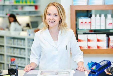 farmacia: retrato de alegre sonriente Mujer del qu�mico farmac�utico de sexo femenino en la droguer�a de la farmacia
