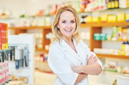 pharmacist: portrait of cheerful smiling female pharmacist chemist woman in pharmacy drugstore