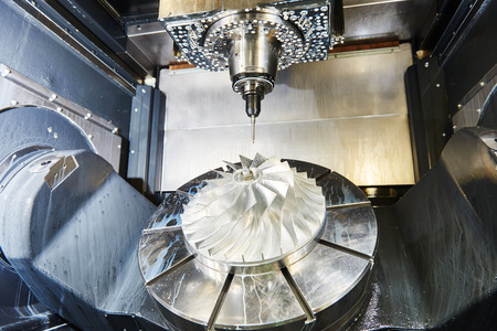 cnc metal working machining center with cutter tool during metal detail milling at factory