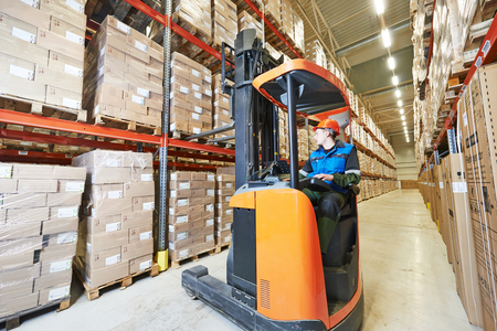forklift driver: warehouse forklift stacker loader stacking cardboxes in storehouse
