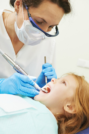 orthodontist: dentist orthodontist female doctor making dental care to child patient at working place