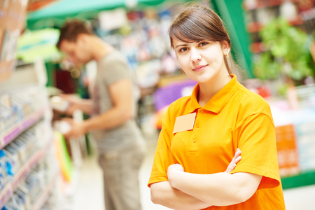 merchandiser: Positive female seller or shop assistant portrait  in hardware supermarket store Stock Photo