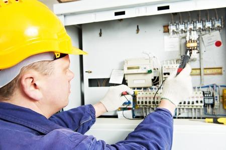 mecanica industrial: constructor electricista en el trabajo con la medición de probador de alto voltaje y la corriente de la línea de energía eléctrica en fuseboard distribución electical. Centrarse en las manos