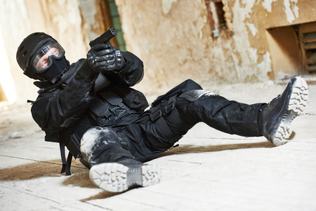 special agent: Military industry. Special forces or anti-terrorist police soldier,  private military contractor armed with pistol ready to attack lying on ground during clean-up operation, mission Stock Photo