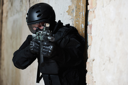 special agent: Military industry. Special forces or anti-terrorist police soldier,  private military contractor armed with assault rifle ready to attack during clean-up operation, mission