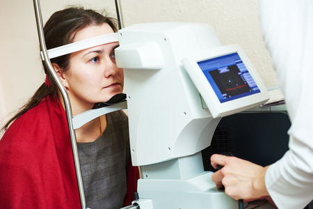 optometry: optometry. Young woman patient under eyesight examination in eye ophthalmological clinic Stock Photo