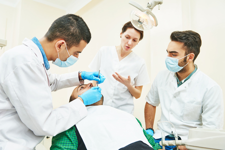 Dentistry education. Female dentist doctor teacher explaining treatment procedure to male iranian asian students in dental clinic Standard-Bild