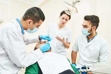 Dentistry education. Female dentist doctor teacher explaining treatment procedure to male iranian asian students in dental clinic Stockfoto