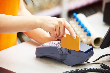 cashier: sale assistant cashier accepting credit bank card and using payment terminal for purchase