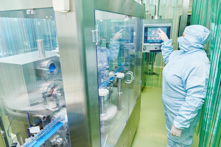 industries: pharmaceutical factory woman worker operating production line at pharmacy industry manufacture factory Stock Photo