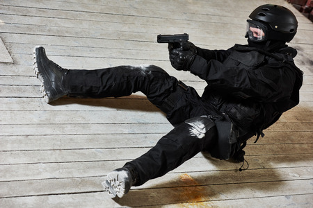 private security: Military industry. Special forces or anti-terrorist police soldier,  private military contractor armed with pistol ready to attack lying on ground during clean-up operation, mission Stock Photo