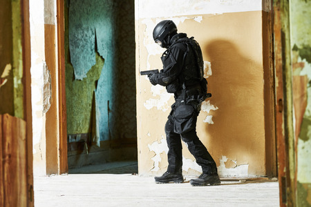 special agent: Military industry. Special forces or anti-terrorist police soldier,  private military contractor armed with pistol ready to attack during clean-up operation, mission