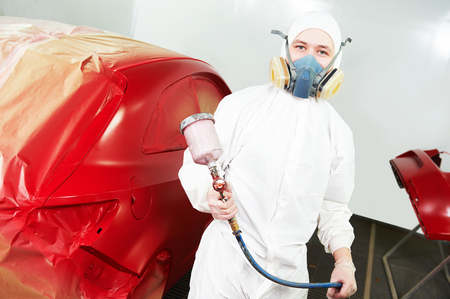 bumper: automobile repairman painter painting car body bumper in chamber Stock Photo