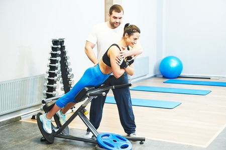 trabalhar fora: fitness and sport concept. personal coach trainer helps woman work out at a gym with heavy weight