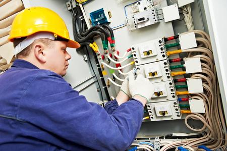 tools construction: constructor electricista en el trabajo con la medici�n de probador de alto voltaje y la corriente de la l�nea de energ�a el�ctrica en fuseboard distribuci�n electical. Centrarse en las manos