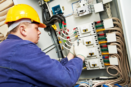 electric line: electrician builder at work with tester measuring high voltage and current of power electric line in electical distribution fuseboard. Focus on hands