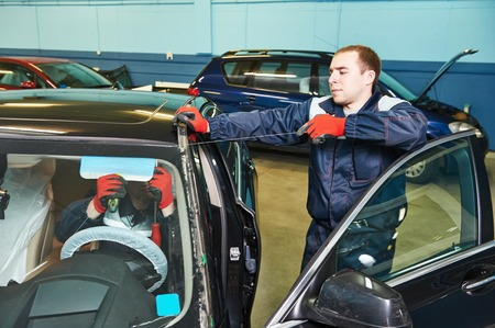 glazier: Automobile glazier worker replacing windscreen or windshield of a car in auto service station garage Stock Photo