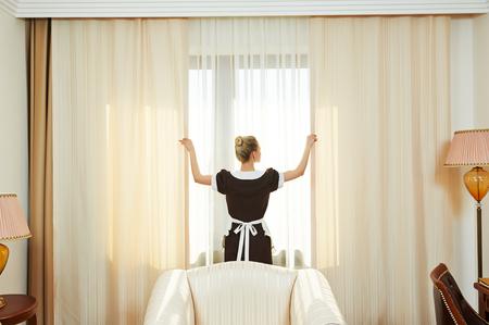 orden y limpieza: El servicio del hotel. trabajador camarera de limpieza femenino abrir las cortinas de la ventana en la habitación