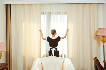 hotel staff: Hotel service. female housekeeping chambermaid worker with opening curtains of window in room