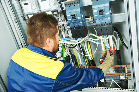 electric circuit: adult electrician builder engineer making electrical measure with equipment in fuseboard Stock Photo