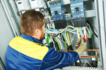 Adulto ingeniero constructor electricista haciendo medida eléctrica con el equipo en fuseboard Foto de archivo - 46546641