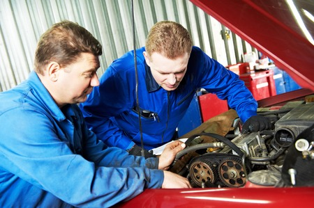 scheduled replacement: two motor mechanic engineers examining timing belt and internal combustion engine of automobile car at repair service station Stock Photo