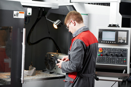 mechanician: mechanical technician service engineer worker at cnc metal machining milling center in tool workshop