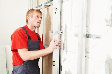 carpintero: Carpintero yesero carpintero con el montaje destornillador sistema de marco de yeso en la pared Foto de archivo