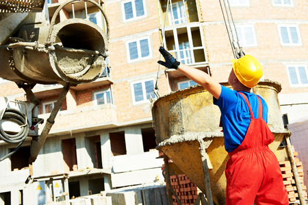 cement solution: builder laborer man working with front of concrete cement mixer at construction site Stock Photo
