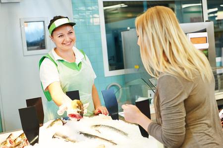 vendedor: vendedor asistente mujer en supermercado venta de pescado fresco con el comprador en la tienda