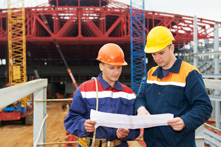 Two engineer builders with blueprint plan at construction site Stock Photo