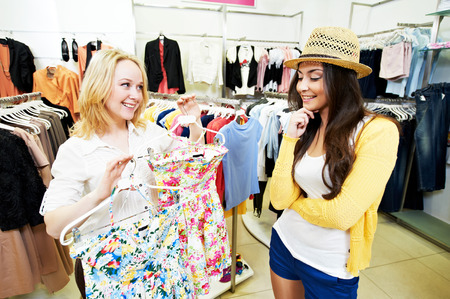 Two Young women with apparel shirt or blouse during garments clothing shopping at store photo