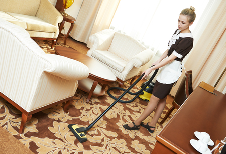 vacuum: Hotel cleaning service. female housekeeping worker with vacuum cleaner in room apartment Stock Photo