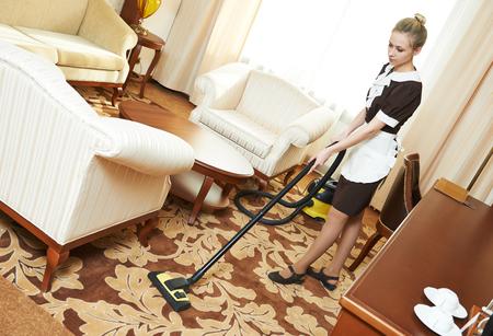 personal de limpieza: Hotel servicio de limpieza. trabajador de limpieza femenino aspiradora en el apartamento de habitación