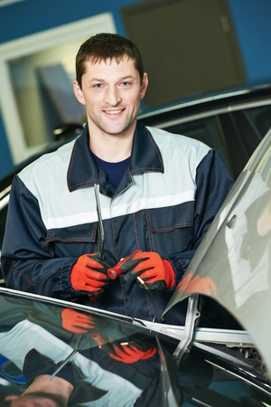 glasscutter: Portrait of automobile glazier repairman at windscreen or windshield of a car replacement in auto service station garage