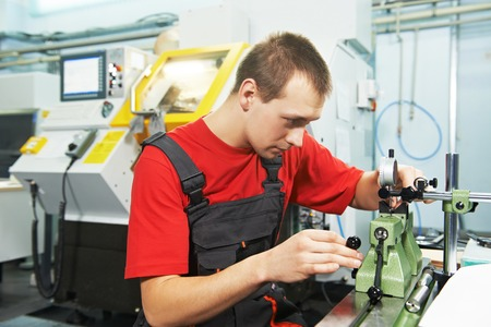 operative: worker in uniform checking quality of processed tool using precise optical device