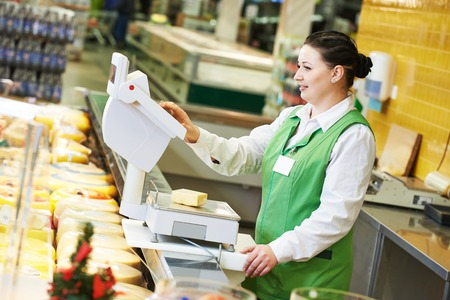 seller woman assistant in supermarket working with scales balance weghing cheese at shop
