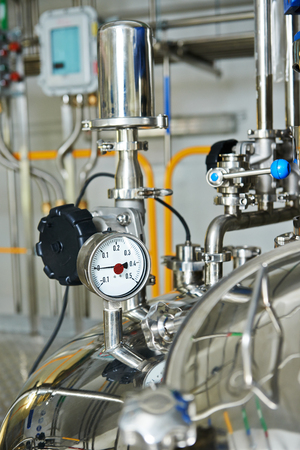 sterility: Closeup of  pharmaceutical factory equipment manometer, pipes, faucet valves, mixing tank on production line in pharmacy industry manufacture factory