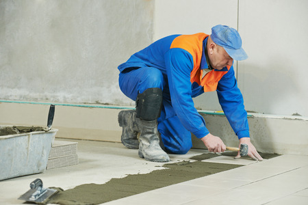 materiales de construccion: industrial tiler builder worker installing floor tile at repair renovation work