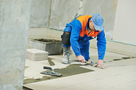 construction material: industrial tiler builder worker installing floor tile at repair renovation work