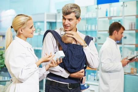 farmacia: Mujer alegre del qu�mico del farmac�utico que da vitaminas a la muchacha infantil en droguer�a de la farmacia